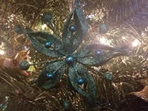 A sparkly teal star on a Christmas Tree.